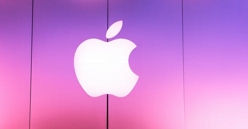 The Apple corporate sign outside a store lit up in pink.