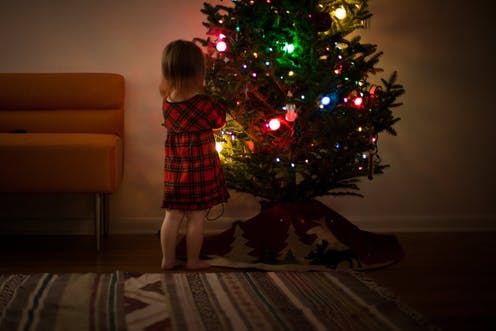Little girl in tartan dress looks at Christmas tree in living room.