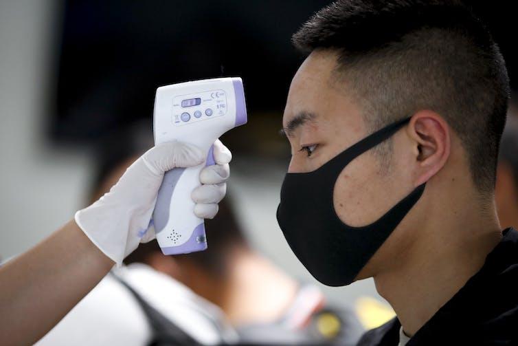 A man having his temperature checked at an airport.