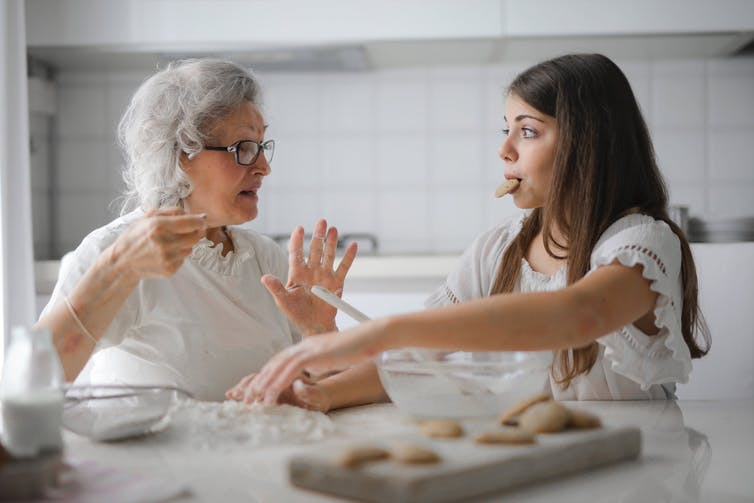 Grandmother and granddaughter having a conversation while baking.