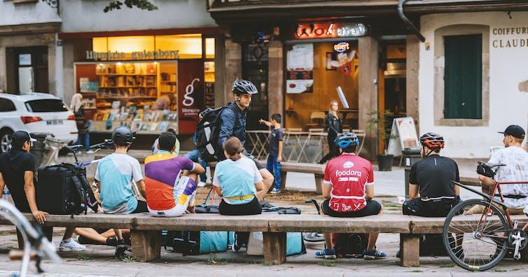 Repartidores sentados en un bando junto a sus bicicletas esperando.