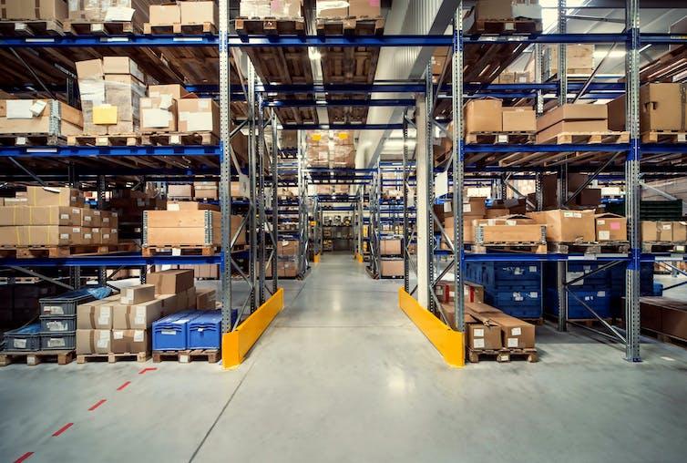 almacén logístico con estanterías llenas de paquetes de diversos tamaños.
