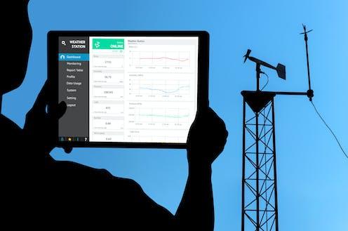 Frente a una torre meteorológica, un operario mira en una tableta datos