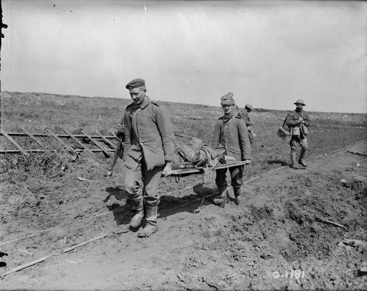 Two men carry a wounded soldier.