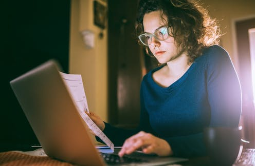 A girl holds a piece of paper while working on a laptop.