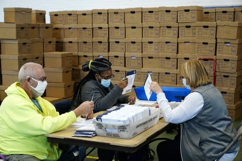 A man and two women look at envelopes with a been similar envelopes on a table between them and stacks of cardboard boxes behind them