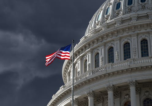 Flag flies at the US capitol, stormy sky