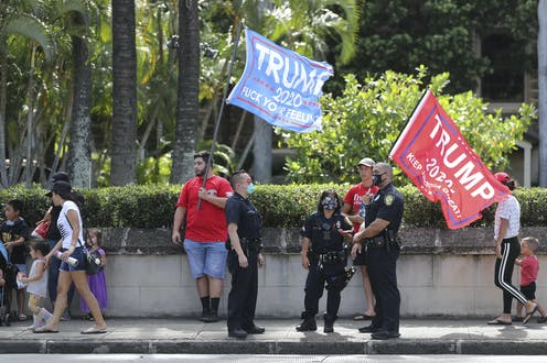 Three police officers stand in front of Trump supporters carrying Trump 2020 flags