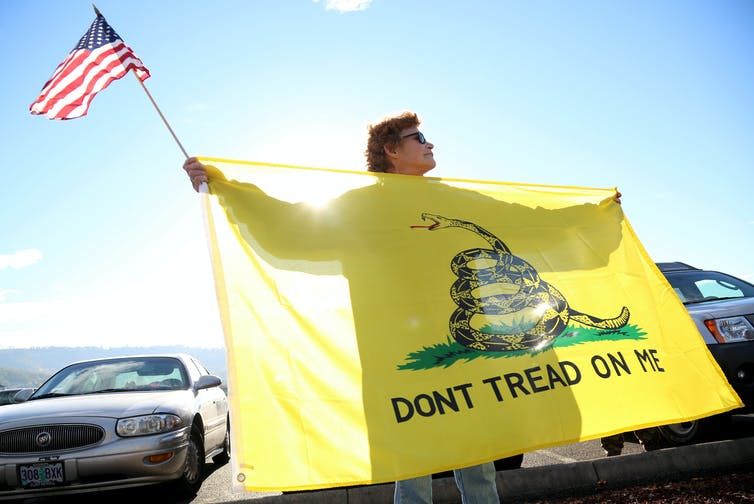 A woman holds the Gadsden flag