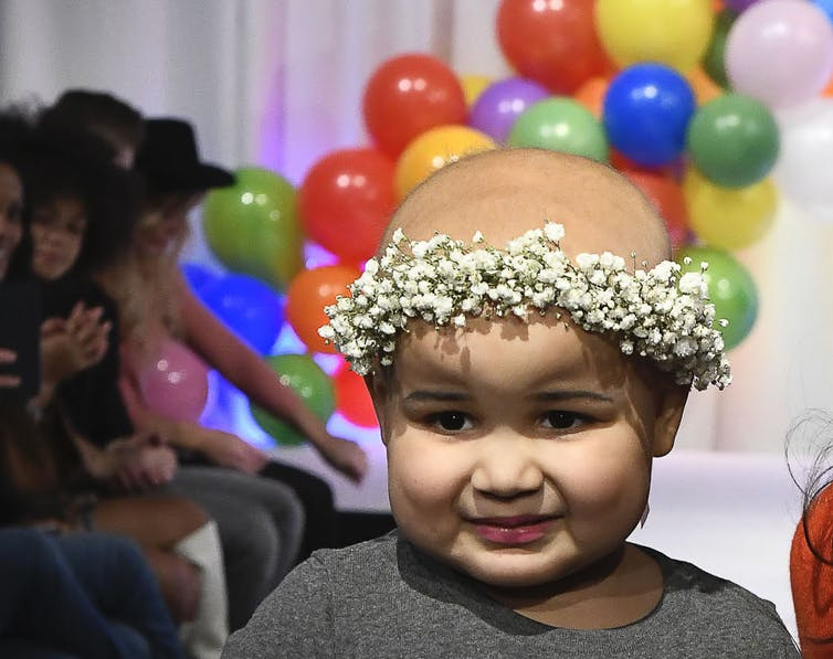 A little girl who has cancer with no hair but a crown of flowers.