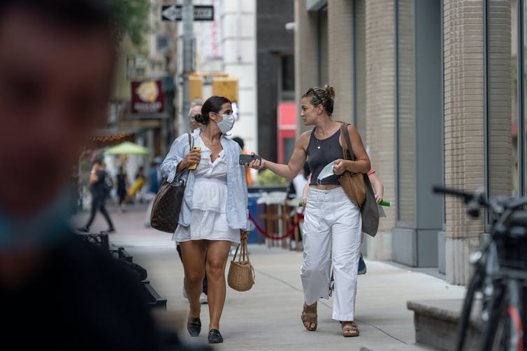 two women talking and walking on the sidewalk, one with a mask on