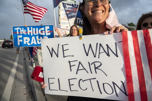 """A US protestor holds a sign reading """"We want fair election"""""""