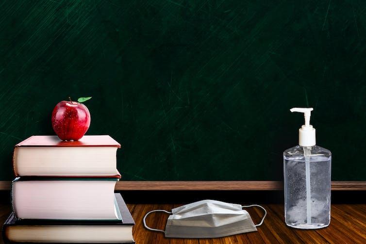 Textbooks, a mask and sanitiser on a teacher's desk.