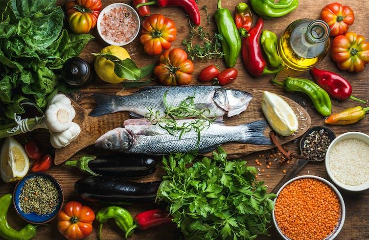 Pescado , pimientos, tomates, perejil y otros alimentos típicos de la dieta mediterránea.