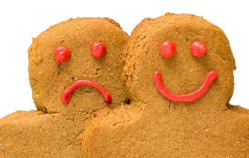 Two people-shaped cookies, one with a smiley face, one with a frown.