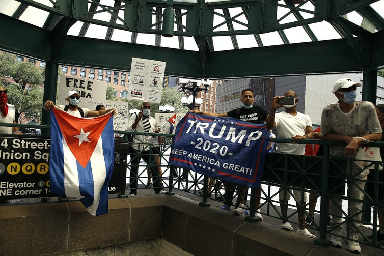 People in face masks hold Cuban flags, pro-Trump signs and 'free Cuba' signs outside a subway station