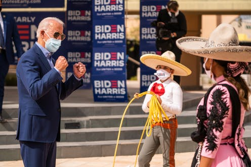 Biden wears a face mask and interacts with children in traditional Mexican wear