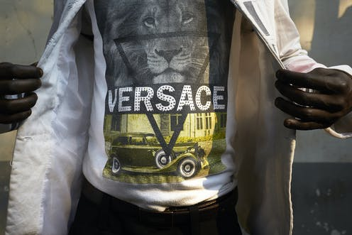 The middle section of a man's body, dressed in a T-shirt with a spangled VERSACE logo, revealed by two hands holding open a shiny white jacket.
