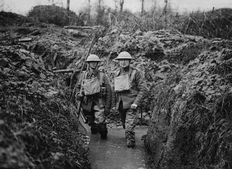 Two World War I soldiers up to their knees in muddy trench water.