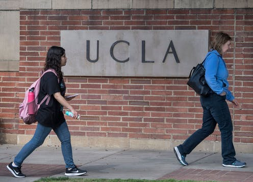 Two female students walk on the campus of UCLA.