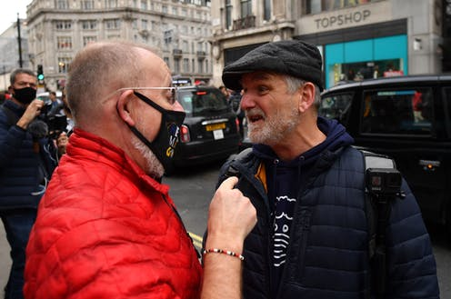 A man wearing a mask argues with a man not wearing a mask
