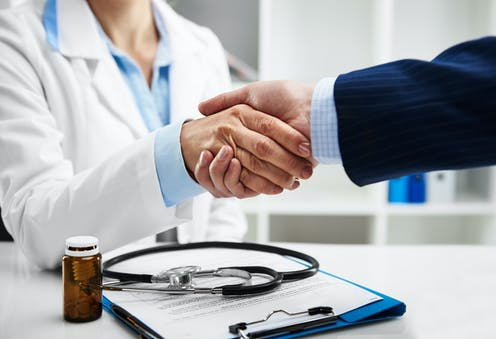 Cropped photo of a female doctor shaking hands with someone in a pinstriped suit.