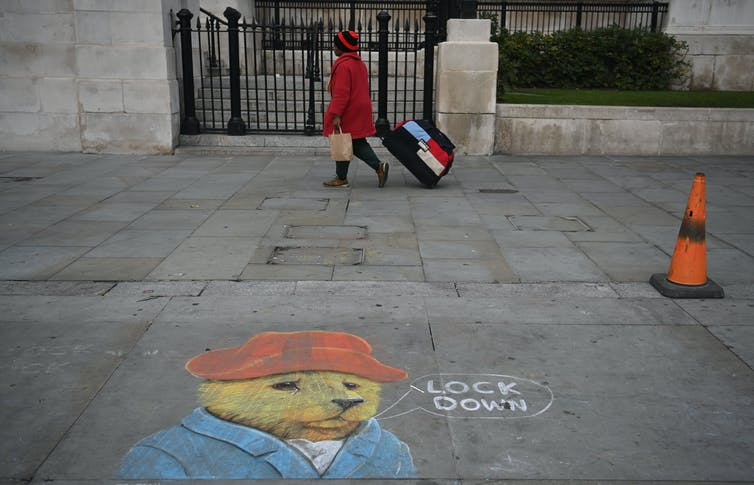 A chalk drawing on a London street of Paddington Bear say 'lock down'.