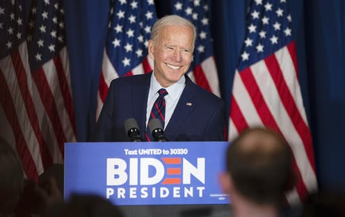 Joe Biden smiling while stood at election campaign lectern