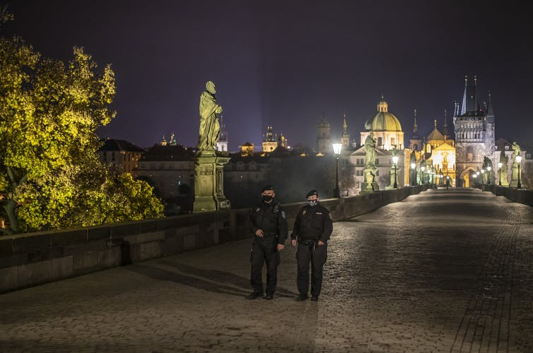 Two police officers walk in Prague.