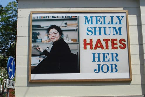 A woman smiling in glasses on a billboard.