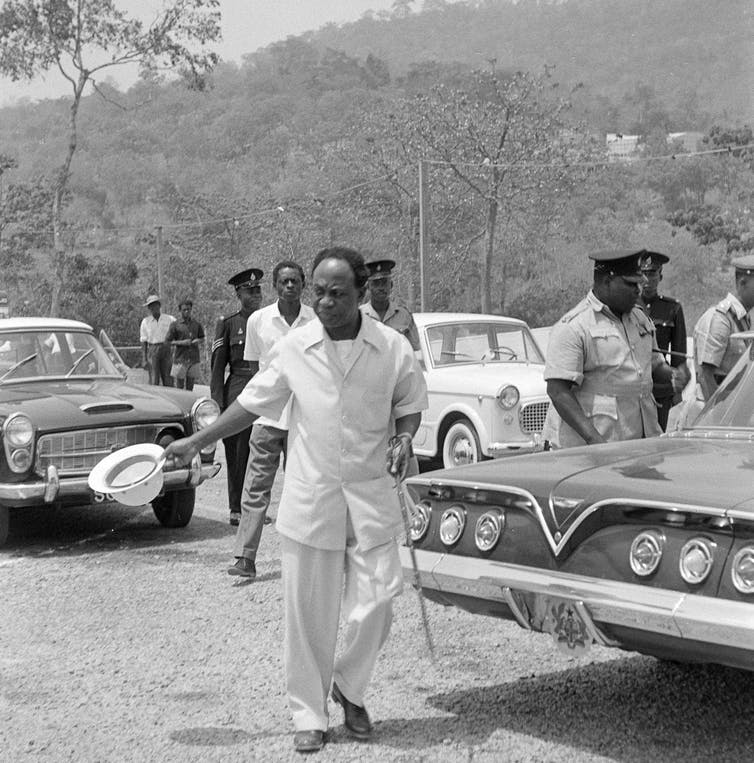 An African man in the foreground wearing a white suit and waving a white hat next to a 1960s Chevrolet car. More men, cars and forest in the background.