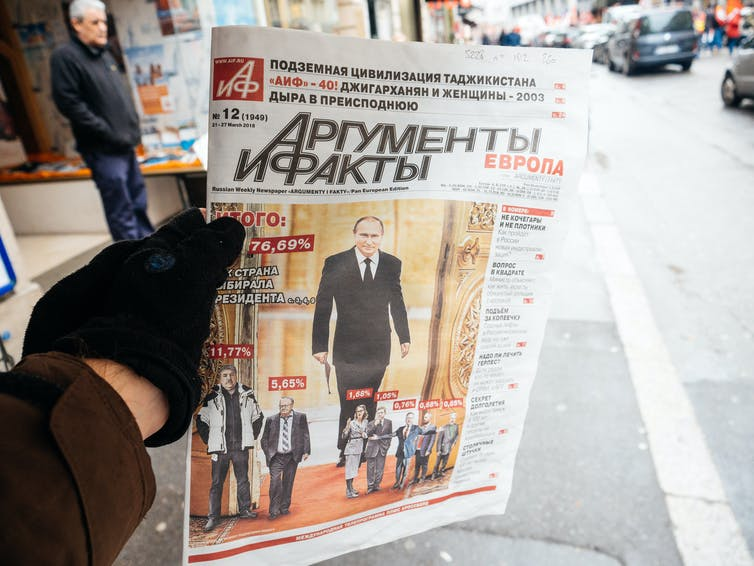 A gloved hand holds a copy of Russian newspaper Argumenty i Fakty.