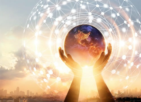 A pair of hands holding a globe of the Earth in front of a sunrise, with an abstract network diagram superimposed.