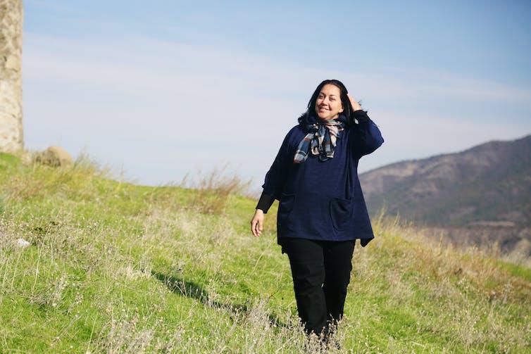 A woman goes walking in a field.
