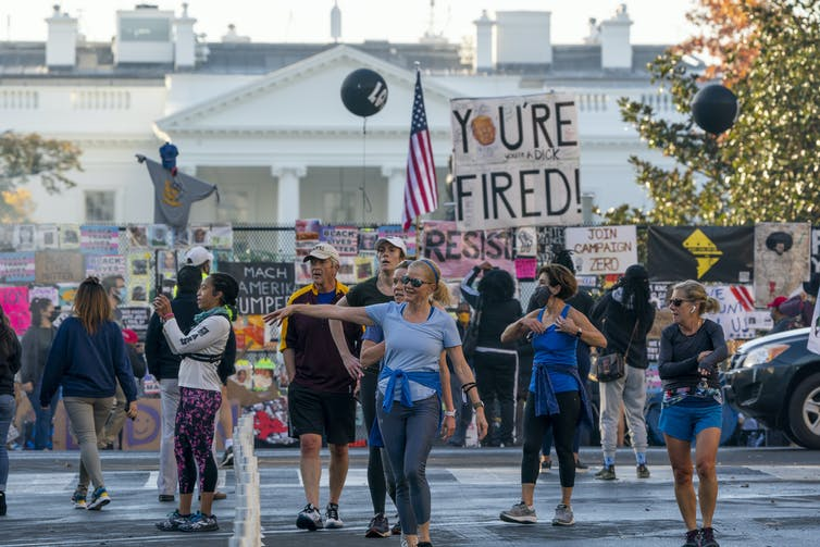 People carrying anti-Trump signs gather with the White House seen in the background.