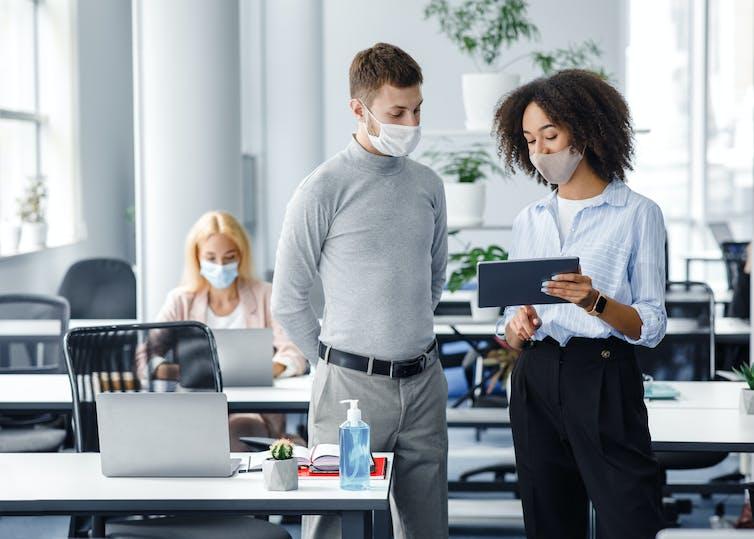 A woman and man talk at work while looking at an iPad.