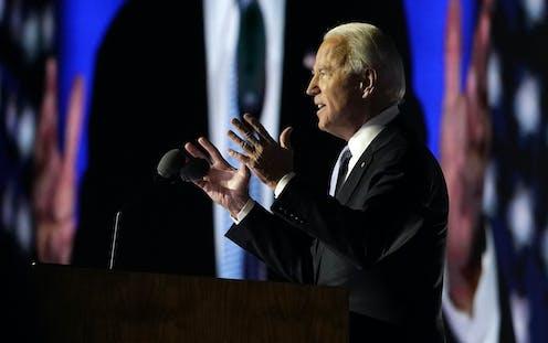 President-elect Joe Biden speaks as he is seen on the large monitor behind him on Nov. 7, 2020, in Wilmington, Del.