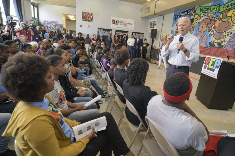 Biden talks in front of a classroom of young people.