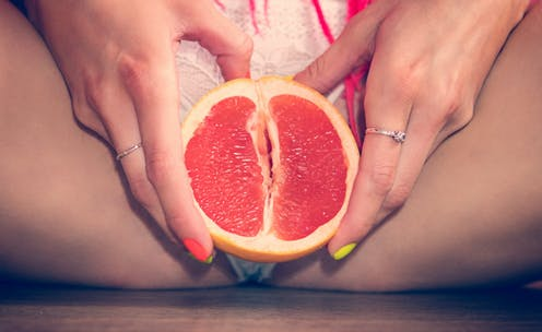 woman holding grapefruit in front of crotch.