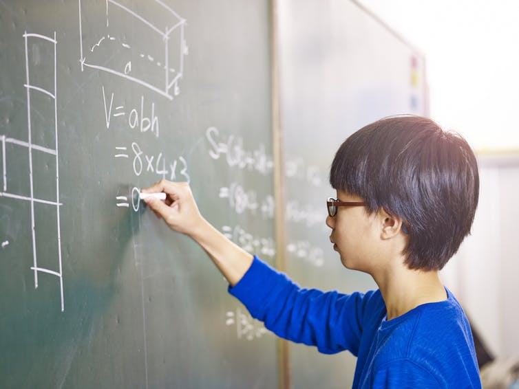 A young Asian boy writing calculations on a chalk board.