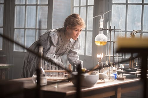 Marie Curie looks at a science experiment