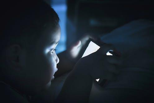 Un niño pequeño a oscuras con el rostro iluminado por la pantalla de un teléfono móvil.