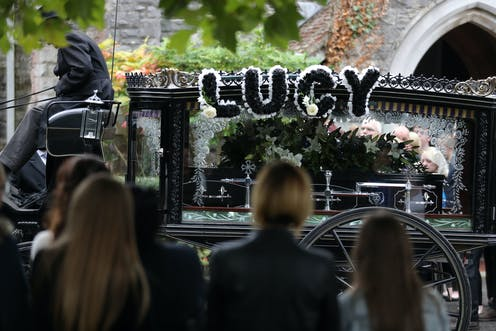 A horse-drawn hearse decorated with the name 'Lucy' carries a coffin.