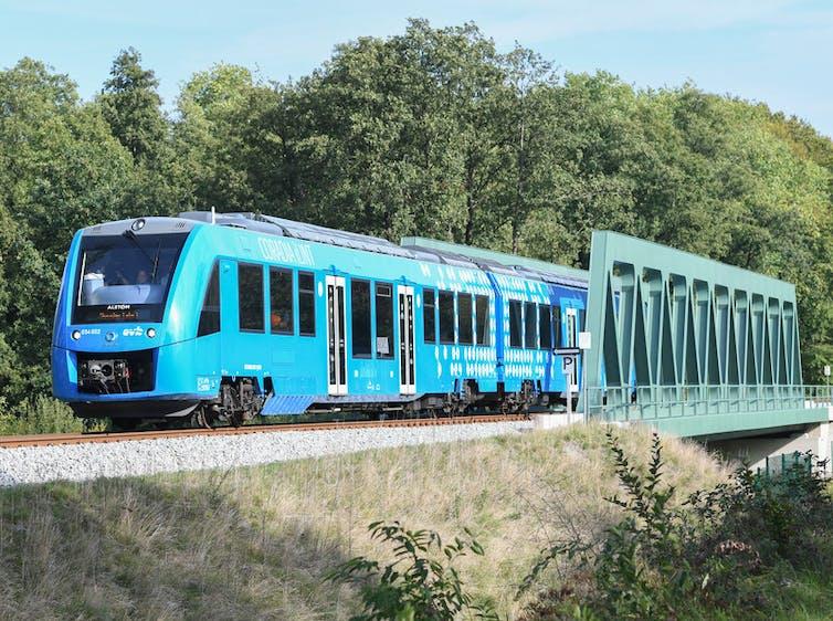 A blue train passes over a green bridge.