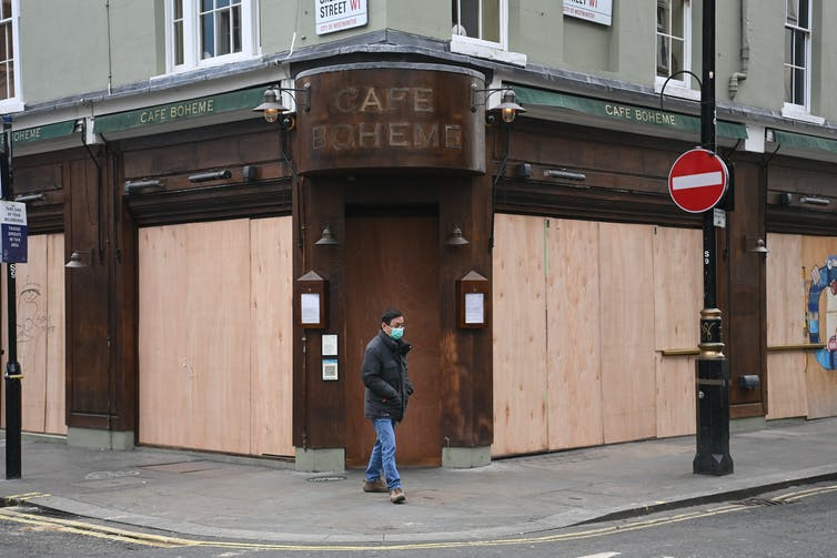 Man wearing a face mask walks past a boarded up cafe.