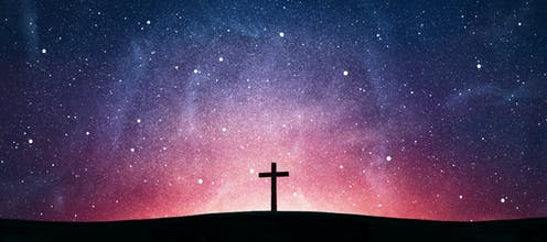 Picture of a wooden cross against a starry sky.