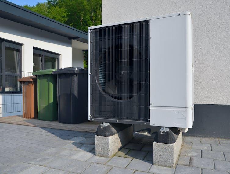 A large fan unit sits outside an apartment building.