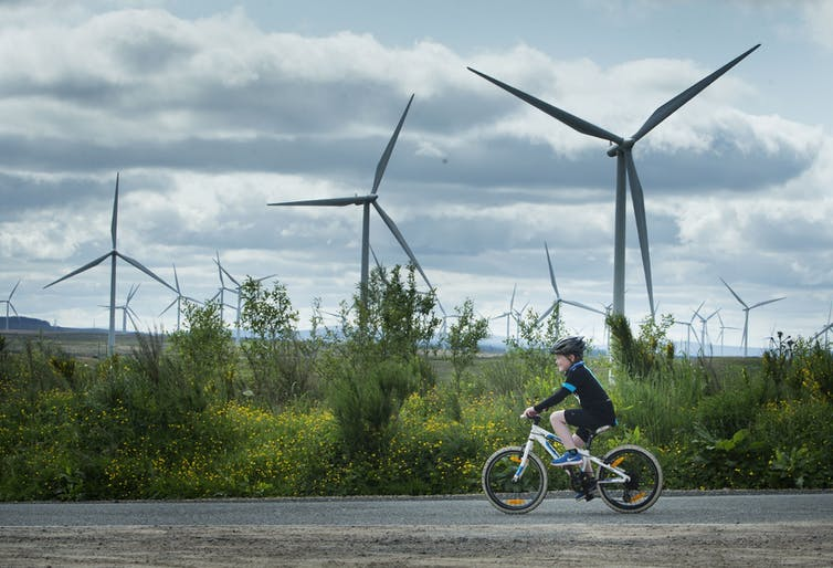Wind turbines turn on a bright day with a child cycling in the foreground.