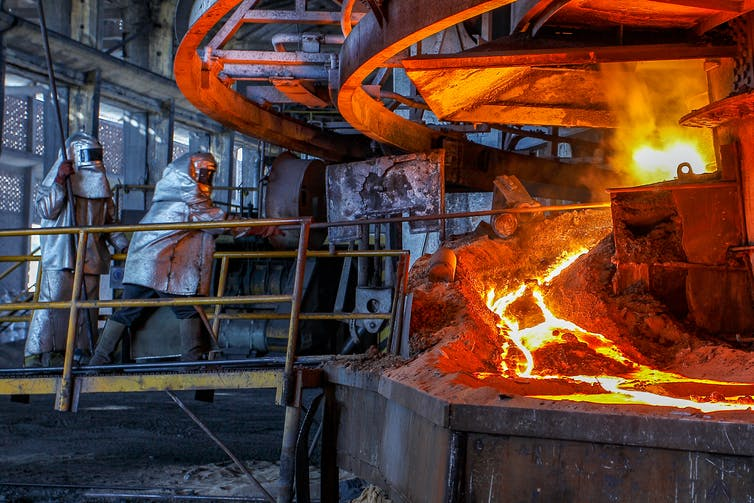 A worker in silver, protective gear stokes a furnace spewing molten metal.
