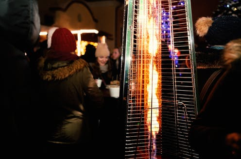 An outdoor heater with people socialising in background.
